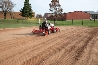 Ballpark Renovator & Groomer in action - In front of you, hardened dirt and dried mud. Behind you, a fresh and smooth infield.