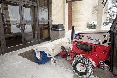 Ventrac 4500Z with Power Broom in Doorway - The Power Broom is capable of clearing areas that blades cannot go or are just not as effective like entryways to buildings.