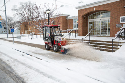 Ventrac 4500 removing snow with Power Broom - Sidewalk and driveway snow removal is not only easier with Ventrac equipped with a Power Broom, Drop Spreader, and fully enclosed heated cab, but is also fun. Reduce the risk of Slip & Fall lawsuits at Hospitals, Schools, Municipalities, and other sites with the Ventrac Power Broom and salt spreader.