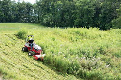 Ventrac 4500 with Tough Cut Mower downhill mowing - Instead of a crew of guys with weed trimmers taking hours, if not days, to tackle hills and thickets like this the Ventrac 4500 with Tough Cut mowing deck can simplify the task enough that only one person can do it all in far less time.