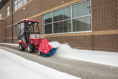 Narrow Sidewalk Broom - Ventrac tractor broom sweeps snow from a school sidewalk